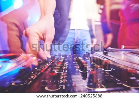 Hand of dj adjusting sound - stock photo