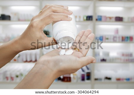 hand of doctor holding Many pills and tablets and medicine out of a bottle on medicine cabinet and store medicine and pharmacy drugstore - stock photo