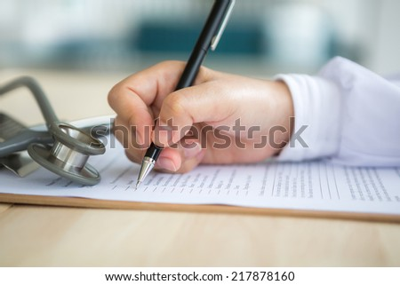 Hand of doctor writing on prescription - stock photo