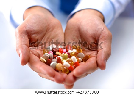 Hand of doctors holding many different pills. - stock photo