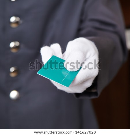Hand of doorman giving key card to hotel room - stock photo