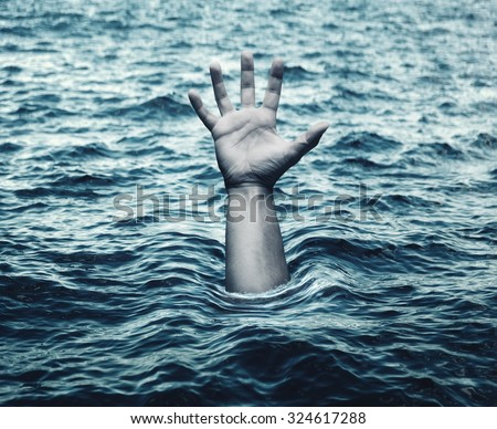 Hand of drowning man in sea - stock photo