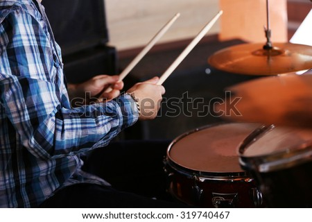 Hand of drummer  with sticks and drums, close-up