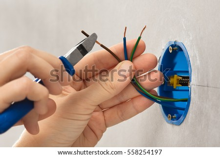 hand of electrician striping the insulation of wires