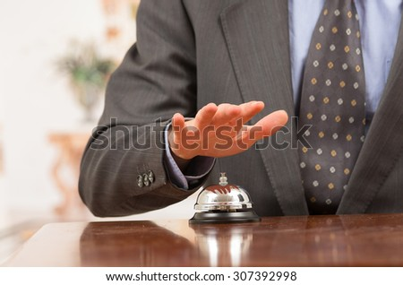 hand of elegant man ringing hotel bell in reception desk close up selective focus