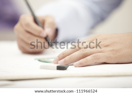Hand of engineer drawing by pencil - stock photo