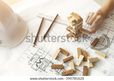 Hand of engineer playing a blocks wood game (jenga) on blueprint or architectural project vintage tone. - stock photo