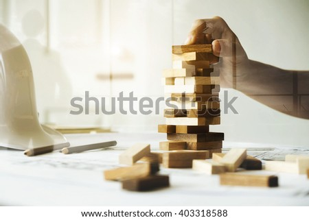 Hand of engineer playing a blocks wood game (jenga) on blueprint or architectural project vintage tone. Double exposure with back side of business man and flight control tower. - stock photo