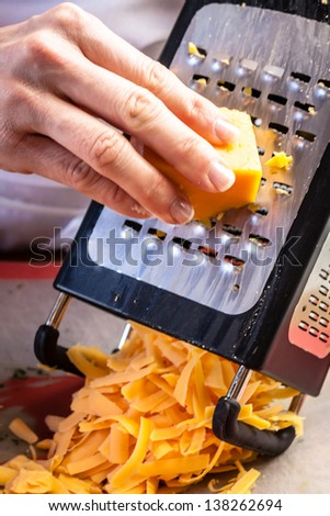 Hand of female chef grating cheddar cheese on metal grater, onto plastic cutting board - stock photo