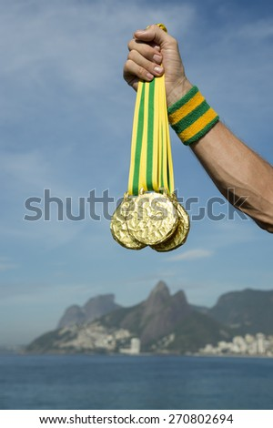 Hand of first place athlete holding gold medals standing outdoors on Ipanema Beach Rio de Janeiro Brazil  - stock photo