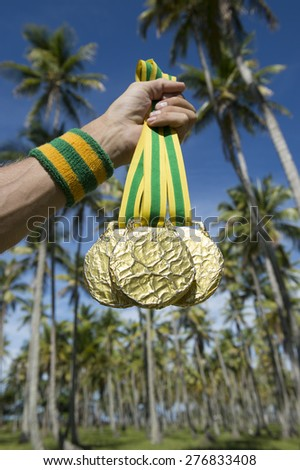 Hand of first place athlete with Brazil colors wristband holding gold medals against tropical background of palm trees - stock photo