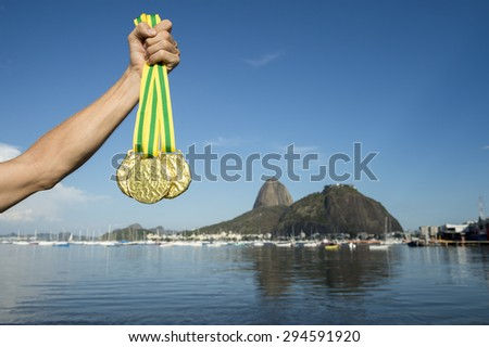 Hand of first place athlete with Brazil colors wristband holding gold medals at Botafogo Beach Rio de Janeiro Brazil skyline - stock photo