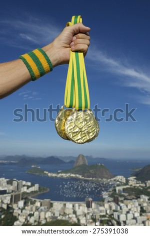 Hand of first place athlete with Brazil colors wristband holding gold medals at Rio de Janeiro Brazil skyline - stock photo