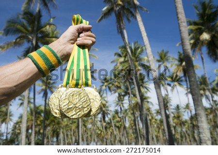 Hand of first place Olympic athlete with Brazil colors wristband holding gold medals against tropical background of palm trees - stock photo