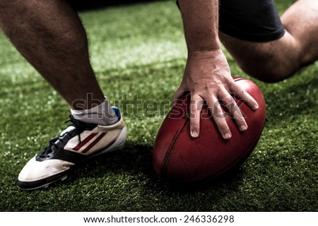 Hand of football player making touchdown - stock photo