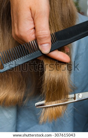 hand of hairdresser trimming hair with scissors