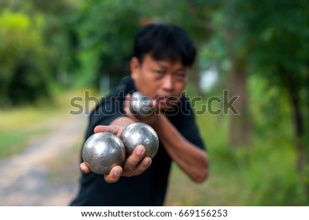 Hand of holding steel ball.A man playing petanque ball.Select focus on blur background.