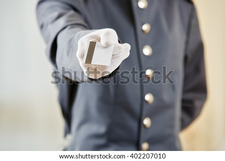 Hand of hotel clerk offering a key card - stock photo