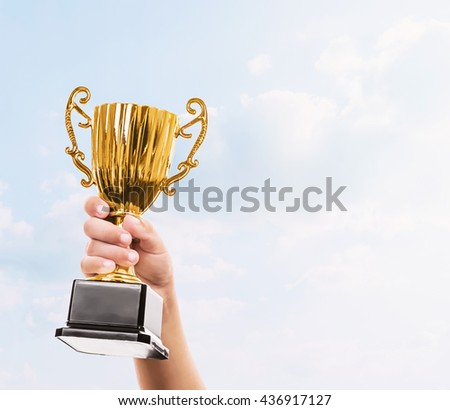 hand of kid holding the golden trophy cup and sky background
