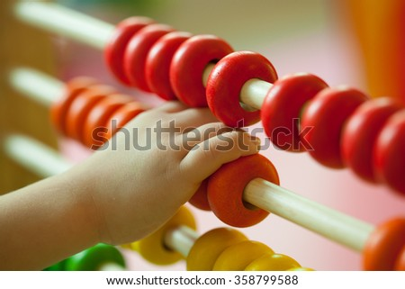 Hand of little boy playing with abacus. - stock photo