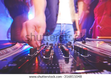 Hand of male dj adjusting sound during disco party - stock photo