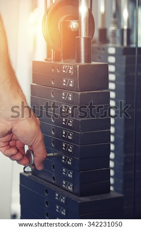 Hand of man adjusting the weight in exercise machine - stock photo