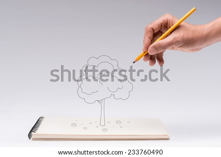 Hand of man drawing a tree with a pencil - stock photo