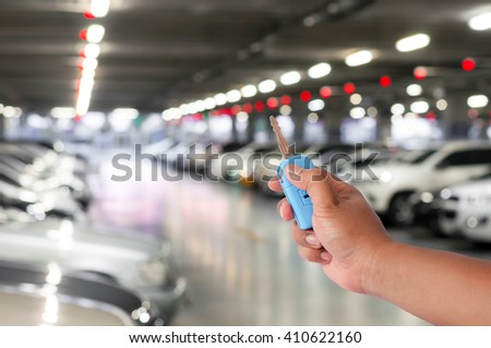 hand of man hold blue car key over blurred car parking with bokeh light Background