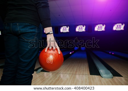 Hand of man player with bracelet holding bowling ball