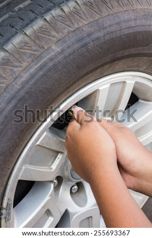 Hand of man pumping air into auto wheel