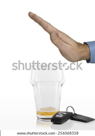 Hand of man refusing any more beer in his empty glass next to car keys on a white background