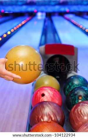 Hand of man, which takes yellow ball for throw in bowling club - stock photo