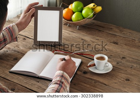 Hand of man writing in a blank notebook on the wooden table. Next on the table is an empty frame. Copy space. Free space for text. top view - stock photo