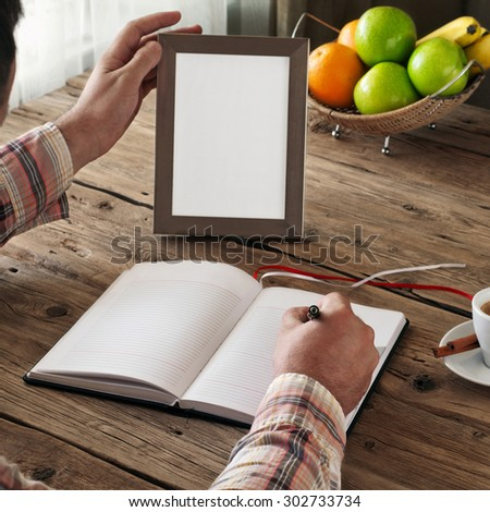 Hand of man writing in a blank notebook on the wooden table. Next on the table is an empty frame. Copy space. Free space for text. top view. Square frame - stock photo