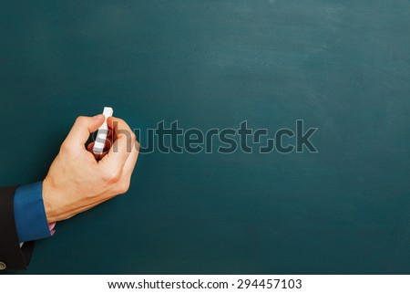 Hand of manager with white chalk on an empty chalkboard