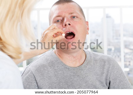 Hand of nurse giving patient medication - stock photo