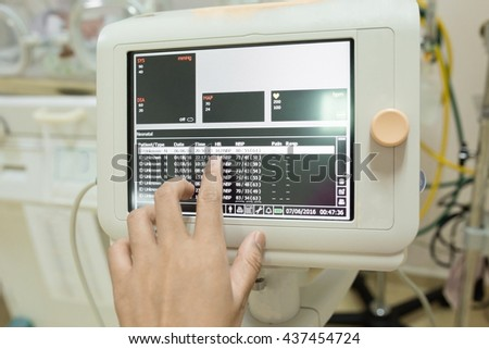 Hand of nurse or doctor control of  medical device monitor  in the hospital. - stock photo