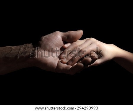 Hand of old and young man in a low key.toning - stock photo