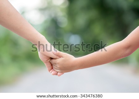 hand of parent and child on the background blurred nature.Mother holding hands baby - stock photo