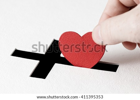Hand of parishioner is inserting heart symbol into hole for donations in form of Christian cross on white background. Idea of sincere devotion for faith with all heart