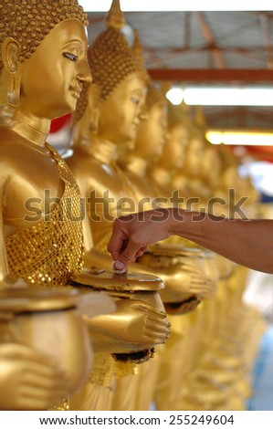 Hand of people donate money at gold buddha statue. - stock photo