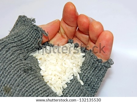 hand of poor man holding a handful of rice - stock photo