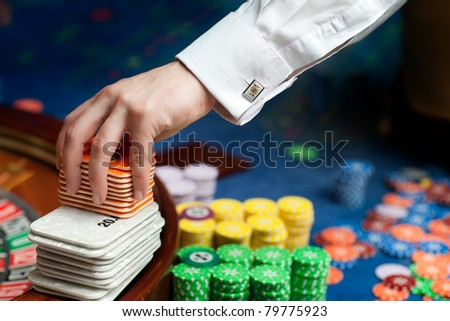 hand of professional casino dealer moving plastic cards