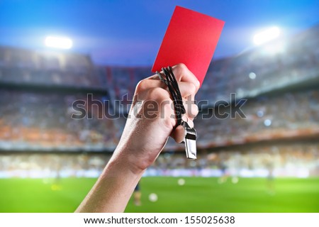 Hand of referee with red card and whistle in the soccer stadium. - stock photo