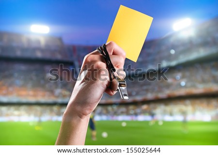 Hand of referee with yellow card and whistle in the soccer stadium. - stock photo