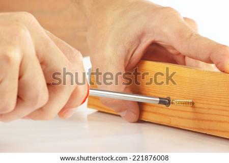Hand of repairman tightening the screw into the wooden block closeup - stock photo