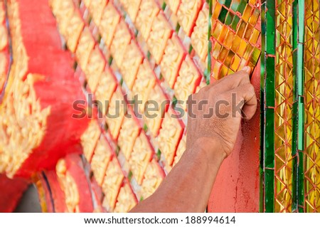 Hand of sculpture artist make a traditional Thai style of buddhist church wall pattern - stock photo