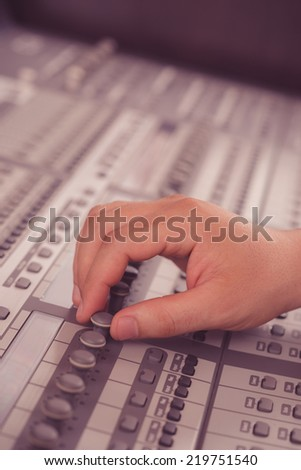 Hand of sound engineer working with music mixer - stock photo