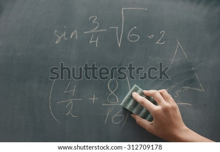 Hand of student studying mathematics and writing on a blackbroard