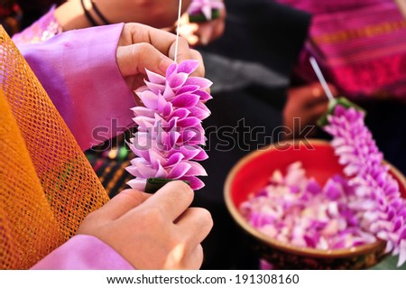 Hand of thai young woman posing artificial flowers.